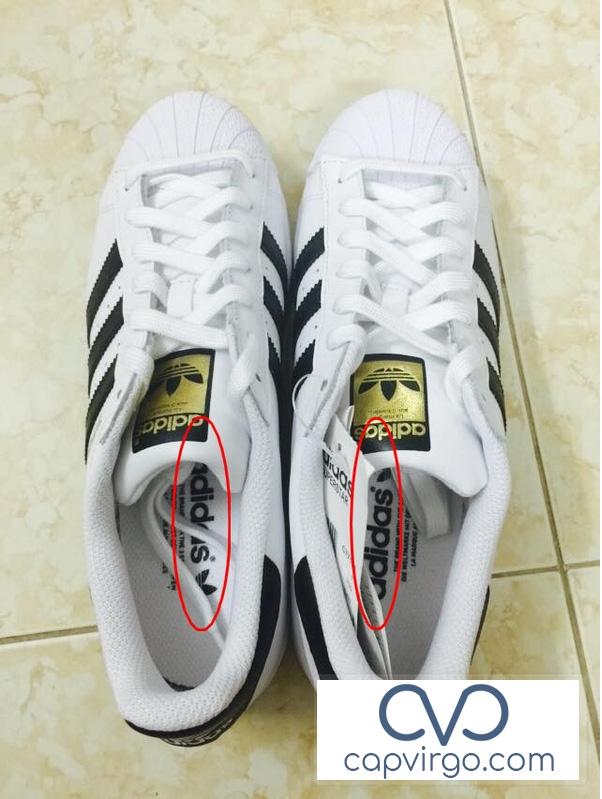 Giày Adidas xịn với tên hãng in trên lót giày ở hai chiếc giày ngược hướng nhau.